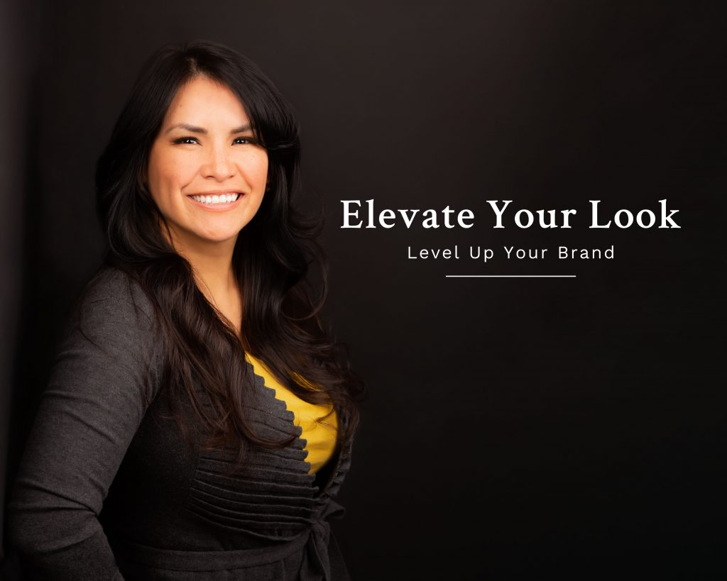 Studio headshot of woman standing against black wall. Text on image reads elevate your look level up your brand.